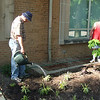 Glenn Rinker waters new plants, while Mitch Cogswell oversees the work.
