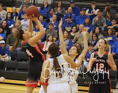 Wildcat Sophomore Destiny Smith (4) attacks the basket over Circle defenders Leah Metzger (14) and Kayla Rushing (23) as teammate Caedyn Reinhardt (12) looks on.