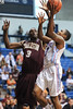 Citadel Bulldogs guard ASHTON MOORE (12) is challenged by Charleston Cougars forward ANTHONY THOMAS (3) as he goes up for the layup in the first half of an NCAA basketball game between Charleston Cougars and the Citadel bulldogs at McAlister Field House.