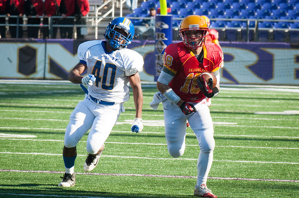 Calvert Hall senior Logan Kurek (18) runs the ball back for an 83 yard touchdown during the 4th quarter of the 93rd annual Turkey Bowl. The touchdown led the Cardinals to a 21-14 win over Loyola Blakefield.