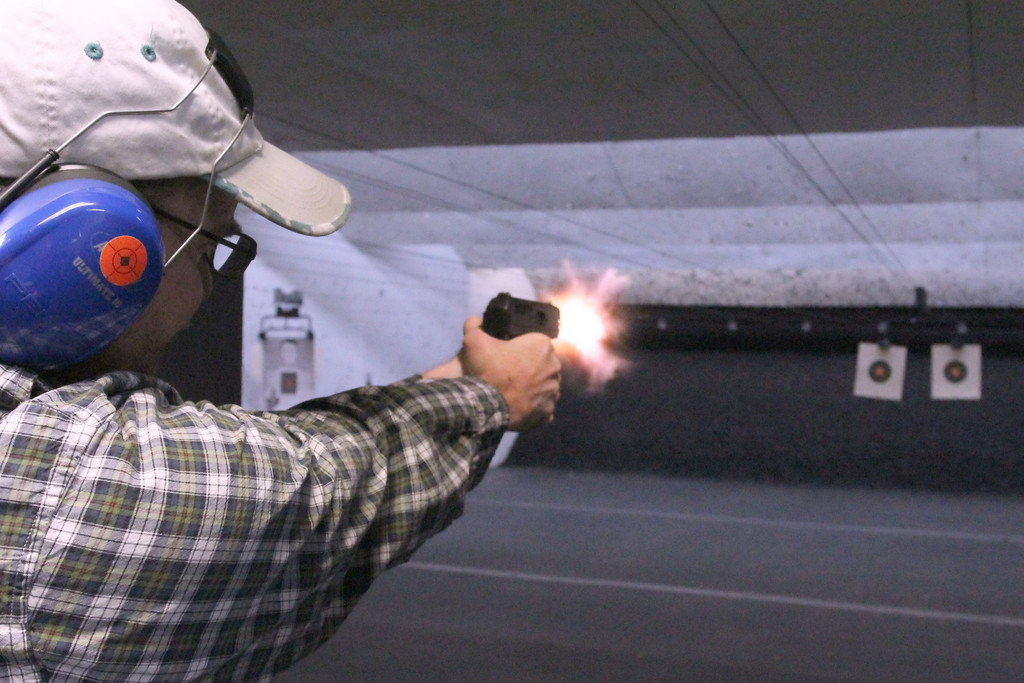 20120213HB Huntington Beach Regional Men of Saddleback Night Out with Pizza and Firing Range on November 14, 2012: Firing-Line Indoor Shooting Range, 17921 Jamestown Ln<br /> Huntington Beach, CA 92647: Justin Strayhorn firing handgun with explosive light coming out of barrel
