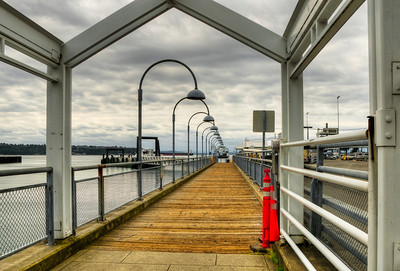 """23 Sep 11.  Another image from the Day in Seattle outing for today and one which serves to illustrate, hopefully well, the concept of the vanishing point. Seattle has relatively """"recently"""" added a passenger only (foot ferry) service to its vehicular service for those wanting to commute across Puget Sound. The outing was my first time to see it, and in truth, didn't actually even realize what it was I was photographing until I got around to working on the images shot that day. Vanishing points serve to give us size relationships, distance, scale, and most obviously, draw our eyes to a specific location.There are multiple sets of vanishing points working in this image, of which my favorite are the arching light poles. Added to those are the superstructure, the railing, the decking, and, to a lesser degree, the clouds, all of which should make you focus on the ferry, small though it may be. I spotted the vessel a ways out and then got into position such that the boat had to come directly under the curved light poles. It could have been a better shot had I caught the boat just a few seconds later requiring some considerable editing, but it was getting larger quite rapidly and I was quickly loosing my desired result. I tried some shots with the boat further back and thus smaller but it rendered the vessel so small as to totally loose the effect. I gave some thought about cloning out the last two """"offending"""" light poles which would have made a more perfect composition, but decided against it primarily because I don't have a good example of a very small ferry to use to fill in the removed portions correctly. As it was, the original required a fair amount of straightening to get this """"correct"""" look  ISO 200; 1/500 sec (middle of 5) @ f/11."""