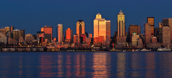I had the opportunity Wednesday afternoon/evening of leading a Seattle Mountaineers Photo Committee photo shoot to capture the full moon rising over the downtown area of Seattle from West Seattle. The moon is full over the city looking easterly in Jan and southerly in June when we shoot from Kerry Park. The group was comprised of roughly 10 folks from the Mountaineers but a few others joined us to inquire as to how best to shoot the scene. We got there early enough to witness and enjoy the sun setting on the architecture of the city for which it is rightly known. We shot the sunset for the better part of 90 minutes before being romanced by a most lovely orange moon. Shortly before the moon arose one of the members inquired why we started so early if we were there to shoot the moon. About 20 minutes after asking the question he got it answered when the setting looked about like this image. I've intentionally over used the noise reduction tools on this image, shot just 15 minutes prior to moonrise, to make for an artistically softer image as it is the shape and color I want to emphasize, not the specific minute details of the buildings, although they are sharply there in the original. ISO 200; 1/6 sec @ f /10 on a tripod.