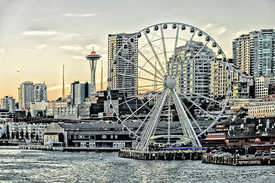 """21 Aug 12.  Seattle has just added a new tourist attraction to its waterfront setting in the form of a large, 42 gondola, Ferris Wheel. It came about rather suddenly from my perspective, is a private enterprise venture, - yeah!!!! - and seems to be becoming a major attraction. We haven't ridden it yet, and probably won't, but our daughter and her family have already paid it a visit. According to the cherubs, it wasn't all that great because it rotates """"way too slow.""""  Of course that might make it a good photographic venture, but I'm not all that excited about the potential. Returning from Seattle last evening via the Bainbridge Island route we were sitting beside it for quite a while and I took the opportunity to photograph it in differing lighting conditions as well as from different perspectives. The image for today is one of those and it has been highly manipulated to get the """"look"""" I wanted. Since a Ferris Wheel is a carnival type attraction in my mind, I've attempted to render the shot with a similar """"feel.""""  To get what I have, I first did my best to control the perspective in ACR, then added a hue/saturation layer, then a tonal control layer followed by a second tonal control layer to multiply the effect, then another set of two hue/saturation layers (to control the effects of different colors), followed by a strong noise removal layer and then finally a very light edge vignette. Nothing difficult, but it does require an idea of where you are going before you begin. Nikon D300s; Aperture Priority; 18 - 200; ISO 200; 1/160 sec @ f /5 on a moving ferry."""