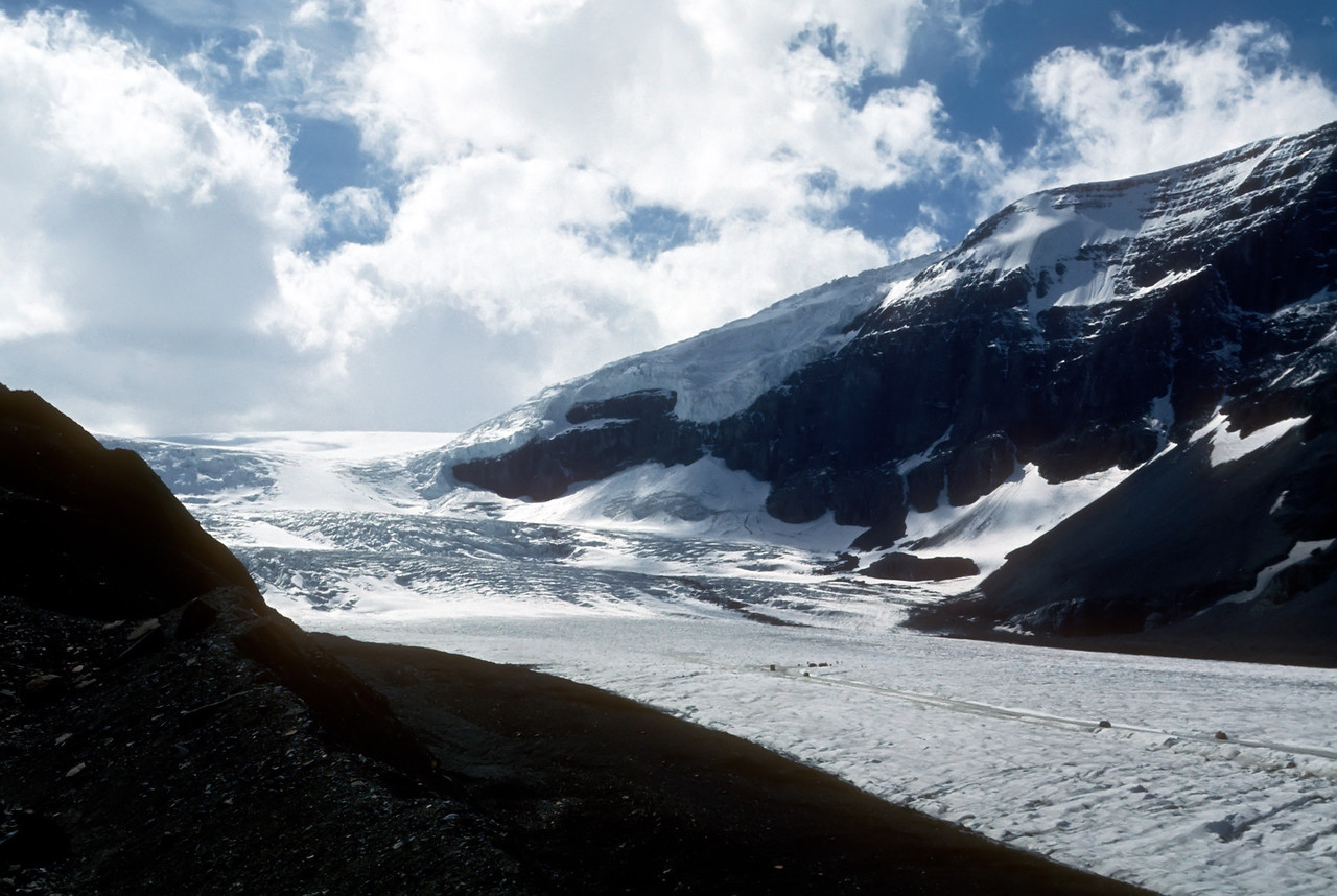 20 Mar 12.  Those of you who keep track of this daily gibberish may recall that I sent an image of the Athabaska Glacier back on the 30th of January. Our visit to see it was in 1973, and it was most impressive. Like most of the glaciers in N. America, it is currently in a retreating phase, but as anyone who studies glaciers learns they advance and retreat and some do it with some apparent regularity. The link above has pictures from various times, and I thought the one from 2005 (sign says 1995) an interesting contrast to the image to its right as well as for what I'm sharing today. To say that the glacier we saw was a bit of an overwhelming experience would be a vast understatement, and perhaps I can put some perspective to that statement by explaining that the small dark blobs you see in the diagonal ice roadway in the lower right hand section of the photo are 22 passenger buses! The dark area in the lower left hand side of the image is also part of the glacier, being a portion of the glacier that has pushed rock up on top of itself as it moves forward. If you still have that image from the 30th (there is a copy of it on the blog) compare it with what I have included here. The 30th image is basically a magnified section of this image, encompassing a section from the middle and moving left. They are individual exposures, one taken to show the enormity of the glacier and another to give a more dramatic presentation. If you were to visit it today I'm rather certain that from this vantage point it wouldn't look much different , but if one were to stand at the toe I think it would drastically different. ISO would have been 100 as it was shot if Fujichrome but I have no exposure data available (memory just not all that good).