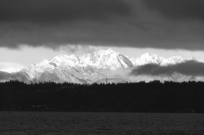 02 Feb 12.   Traveling across the pond this a.m. to work on the house, I left in rain, drove through a rather nice snow fall, and then arrived at the ferry terminal to be greeted by a most spectacular storm crossing in front of the Olympic mountains. As I watched it break apart it partially obstructed the mountains providing for a very dramatic view. I figured since the rock theme was going well I'd just continue it but with some local rock this time. From the perspective of rock, many folks out our way consider the two mountain ranges, the Olympics on the west and the Cascades on the east to be the real rock stars of the Pacific Northwest. I played with this in color as shot be decided that it lent itself well to a B&W image, reminiscent of one of the greatest Seattle photographers of all time, Joesph Scaylea, so I changed it to that format. I removed what was likely a Bald Eagle from the clouds in the upper mid right because it was more a blur than a silhouette but left in the Seagull in the lower left corner. Other than a small bit of noise abatement, the image is right out of the camera, minus the color of course.  ISO 200; 1/320 sec @ f / 9.