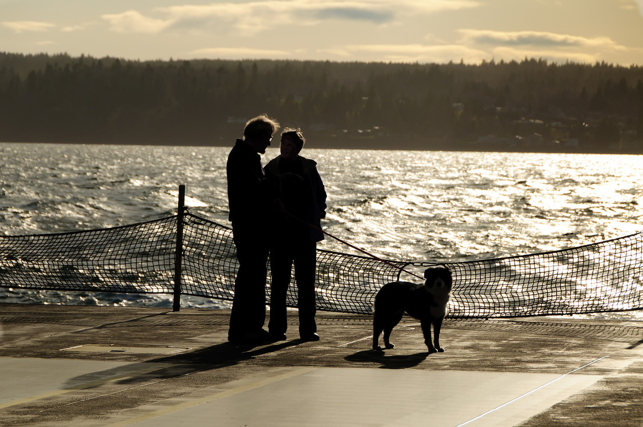 23 Mar 12 .  	Returning home from working on the house a couple weeks ago I noticed a couple with their dog standing as close to the stern as allowed looking back at the Olympic Mountains and in the general direction of the Kitsap Peninsula as if trying to hold on to a particular experience or memory. That offered an opportunity for several different approaches in creating the image, and I elected to go with an almost total silhouette, but not totally black. IF you concentrate hard enough you can see the faces of all three, but I had to manipulate the original RAW image somewhat to make that happen. At first glance you won't see their faces, which is exactly what I wanted, but they are there. In retrospect I probably should have gotten a model release, but at the time of the shoot I didn't realize I had as much detail available as I did. That said, I find it highly unlikely that anyone of this mailing list would recognize the couple and/or their dog. Even exposing the couple to the degree that they went almost solid black, I still had too much light falling on the water which had to be handled carefully as a layer in Photoshop and selectively darkened. As the area was quite blown out in the original, getting the water to blend in took a bit of effort, but eventually I got it sufficiently under control that I think it looks O.K. for sharing.with you. ISO 200; 1/2000 sec @ f /10.