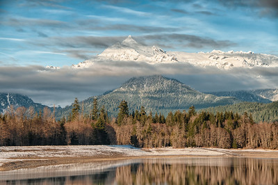 24 Jan 13.  The last leg of our Highway 20 trip last Tuesday saw us driving up to the Baker Lake area. Formed by a dam, Baker Lake offers some nice scenic areas in which to ply the art. Below Baker Lake proper there is another very small mud dam that forms another lake, but it is very small and I have not been able to find the name of it yet. There is a nice park associated with this small dam and plenty of camping area for those so inclined. You can also drive right out to the end of the dam, and from what I can tell the roadway across the top of the dam is open seasonally, or at least that is my perspective as I've only been there late in the year and both times it was closed. But you can walk out there if desired or just remain at the campground end and shoot, which is what I did on this last trip. Looking out over the lake you can see Mt Baker to your left, or at least it topmost portion, and directly across from your lake viewpoint,  Sloan Peak in the Henry M. Jackson Wilderness. At 7835 feet it is by far not the most impressive peak in the Cascade range, but in as much as it looks a lot like the Matterhorn it will get your attention, even from a distance. And even though most of its sides present a difficult ascent, on one side is a scrambling trail all the way to the summit. While we were there it was playing a very active game of peek-a-boo with several layers of clouds, such that I thought of originally naming this image, layers. The temp was about 28ºF with a small amount of wind, so it was a bit chilly, but well worth being there. Nikon D300s; 18 - 200; Aperture priority; ISO 200; 1/640 sec @ f / 8.