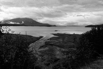 12 Mar 13.	Driving around the greater Juneau area last September I passed numerous little curves in the land which had bodies of water associated with them and each, I'm rather certain, if anything like the peninsula on which we reside, had its unique name. Unfortunately I failed to see most of them and that includes the image for today. In the original there was a rather interesting play of red and green color on the patch of land at the bottom of the scene where the creek enters the bay, as well as some foreboding clouds. It was the contrast of the clouds against the strip of color that caught my eye. But as much as I liked the color, I like it even better in monochrome, so it became this week's entry for B&W Tuesday. I've brought out the detail in the clouds just a bit, and of course converted it to B&W, otherwise, this is how it looked on a cold, windy, temporarily rain free morning. D800; 18 - 200; Aperture Priority; ISO 200; 1/400 sec @ f /8.