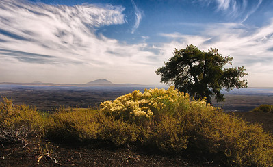 25 Mar 13	Here is another of the older images from our trip in '09. We are at Craters of the Moon National Monument and Preserve in SE Idaho, and if you haven't visited this piece of the National Parks system you should put it on your list of things to see the next time you visit the area around Yellowstone/Grand Tetons National Parks. In fact, it should be the first stop on your visit to the three areas, as it sets the stage for what you will be seeing in the other two. Broken Top Mountain, the summit of which is the setting for this shot, is a easy to moderate climb up a 45 degree angles climb composed mostly of cinders, so while it is not really difficult, it does take a bit of time if you are not in your teenage shape. The view from the top will vary of course depending on atmospheric conditions which were rather nice on our first visit and snowed out on our second visit 8 days later. But both visits were equally nice, we saw different things on both days, and I'm anxious to visit it once more. You are looking east toward Big Southern Butte, about 25 miles distant. The Apollo astronauts trained here in preparation for walking on the moon. That should give you a hint of what it is like and what you could see. I've used some of the newer software tools to present this lovely location in a manner that I hope may entice you to visit. D300; 18 - 200; Aperture Priority; ISO 200; 1/250 sec @ f /16.