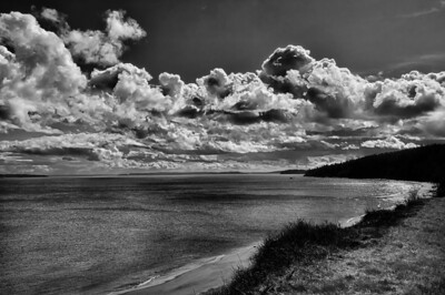 05 Mar 13.  It being B&W Tuesday, we of course will be looking at something in that venue for today. Now if Port Townsend is the view from the north end of Fort Flagler, today's shot, albeit at least in that direction, is the view from the south end. While we were visiting there was a bank of some rather spectacular clouds hovering over the Sound, so I thought it prudent to try and capture them. The original shot is rather nice in its own right, but shooting - well, converting in reality - in B&W, and using a red filter to make for a bit more drama, resulted in what I thought was a rather nice shot. All of this is of course nothing different from what could be done in the days of the wet darkroom and film. But I employed one additional step which wasn't possible in the wet darkroom and added a bit of fine structure enhancement to the clouds. Now that gave them some real punch which I hope you might appreciate. D300s; 18 - 200; Aperture Priority; ISO 200; 1/800 sec (needed the speed with one hand in a sling) @ f /13.