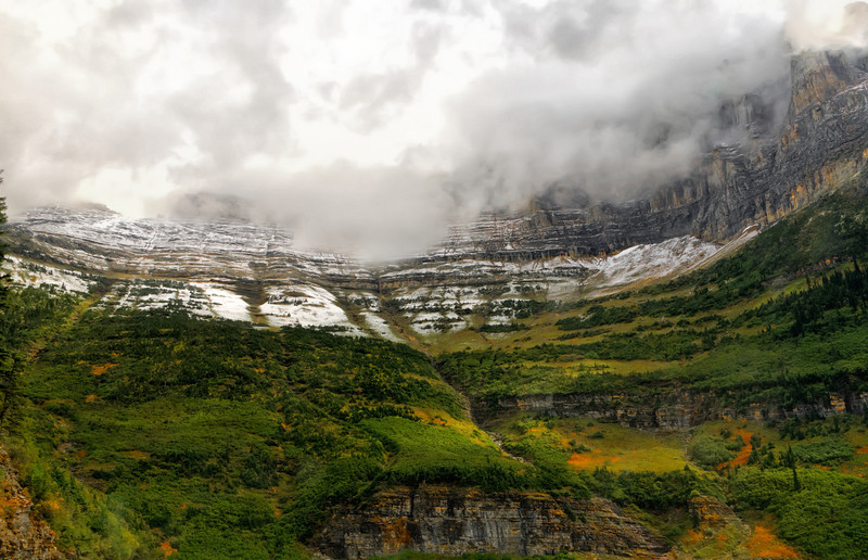 """30 Oct 13.  For those of you familiar with Glacier National Park, today's submission was taken just beyond the viewing site for the 492 foot high Bird Woman Falls. I shot it standing in the road, so the road would be just below the bottom of the image. There was a very small portion of the road in the LRH corner, but it was more distracting than it was providing helpful information, so I loped it off. The clouds were really rolling up the mountainside, putting on quite a show, so we stopped and shot for perhaps 30 minutes in this particular location. Apparently a lot of others were also enjoying the show, because at times the parking area was overflowing. The color we had come to shoot was just barely beginning to show, so I've """"cheated"""" a wee bit and enhanced it to what it might have been, and likely was, about a week to 10 days later. One of the most attractive aspects of this park for my taste would be the rock formations, be they pebbles or mountains. There is so much red, in various shades, in these rocks that one is hard pressed not to be spending a goodly amount of time just looking at them. Take a good look at this image to get an idea of what I mean. There is more color than you might realize with just a quick look-see. Since Wednesday is the day I'm supposed to try for something fine art, my approach for this image was to try and make the clouds """"active."""" Slide back from your screen a few feet and perhaps you will get the feel that they are moving outward towards you, and they were us when I took the shot. Here is how I did this. Starting with the base image, I began by cropping out extraneous material, then did some global contrast adjustments. Then I performed some rather strong detail enhancement to the clouds and to a lessor degree the rocks. That effort was where I tried to make the clouds seem real. Next I did a slight red increase as I mentioned earlier, followed by a creative layer addition which was reduced in opacity to just 37% of the creative e"""