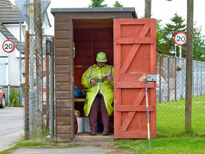 A school crossing guard in Invergordon, Scotland, finds a dry and quiet spot.