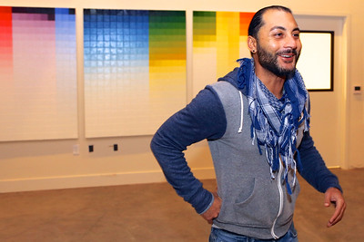 Ali Setayesh hangs his art in the Community Room at the Warehouse Artist Lofts at 1108 R Street in Sacramento. (Photo by Joan Cusick)
