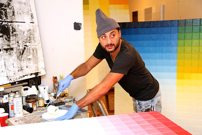 Ali Setayesh prepares art to be hung in the Community Room at the Warehouse Artist Lofts at 1108 R Street in Sacramento. (Photo by Joan Cusick)