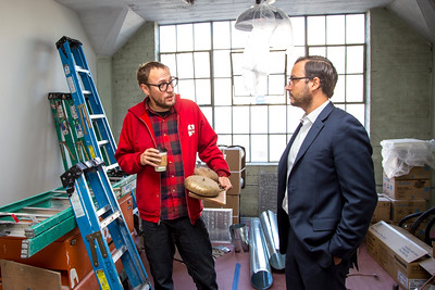 Artist Shaun Burner confers with Ali Youssefi of CFY Development, who oversaw the construction of the Warehouse Artist Lofts on R Street and the installation of local art projects. (Photo by Joan Cusick)
