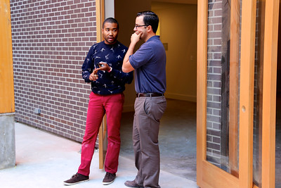 Curator Tre Borden (left) discusses art projects with Ali Youssefi of CFY Development, who oversaw the construction of the Warehouse Artist Lofts on R Street. (Photo by Joan Cusick)
