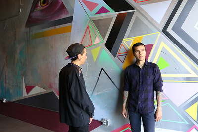 Irubiel Moreno (left) and his brother, Chris, who work together as K.I.D.S. Art Collective, discuss finishing touches to their geometric mural in WAL's 12th Street elevator lobby. (Photo by Joan Cusick)