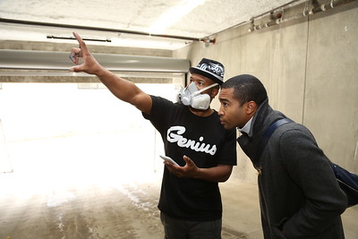 WAL Curator Tre Borden discusses a garage mural with Demetris 'B.A.M.R.' Washington. (Photo by Joan Cusick)