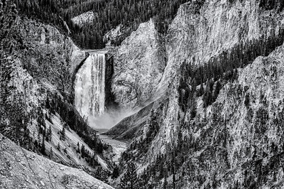 "14 Jan 14.  One of, if not the most, challenging aspects of playing photographer when visiting commonly accessed areas, is that of coming up with a shot that has not been taken before. With the millions of folks taking pictures today, that is a foreboding challenge. During our visit to Yellowstone last October there wasn't a lot of opportunity to get off the beaten path to get the never before taken images, but I'm hoping to change that in 2014. Today's submission is a shot that was taken from a spot that is likely visited by more than a million folks annually, so I've elected to share it in B&W which should be appropriate for B&W Tuesday. This is a shot that works very well in color, and in fact the color version of it came out quite nicely in that I gave it some artificial sunshine that rendered it well. But for today I elected to do some manipulation of the textures in the stone that hopefully substitutes for the effect normally provided by the missing color. I suggest you observe this image from a viewing distance of perhaps four feet from the monitor, assuming you have a ""normal"" sized monitor. For those of you with the big screens, I suggest you add a foot or two. I've never seen a shot of the Lower Falls of the Grand Canyon of Yellowstone rendered in black and white, so I'm hoping that this photo is unlike any you've seen prior. I've left the falls and trees alone, adding the detail enhancement only to the rock. To get to this look I started with the base background color layer, duped that and changes the blending mode to overlay which I applied at 32% ; then ran a global contrast adjustment but not to the falls; then added a color and contrast adjustment (this gave me the final color image I was after); then ran a B&W conversion, and finally another manipulation  concentrating only on the fine detail. Nikon D300s; 18 - 200; Aperture Priority;ISO 200; 1/250 sec @ f / 7.1."