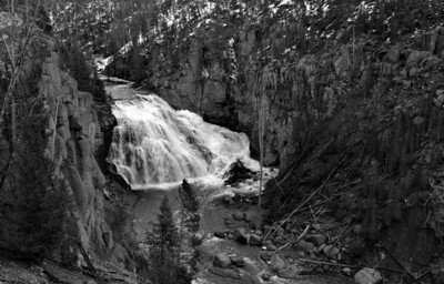 03 Jun 14.  Entering Yellowstone from the wet side, your first decision point is at Madison Junction where you must decide on which direction you want to travel, NE or S. Taking the NE approach you travel maybe 5 miles when you come upon Gibbon Falls. You can't miss it as there is a very large parking lot, lots of railed walking area, and a grand view, to say nothing of the warning signs and reduced speed signs. It is worth a visit and while it doesn't have the spectacularly place viewing stands at the top edge of the falls as in the Upper and Lower Falls of the Grand Canyon of Yellowstone, with a bit of work you can get a reasonably nice shot. It looks very different in the spring than in the fall, but it presents well in both seasons. I'm rather certain it isn't all that bad in the summer either. This shot was taken near the end of the railed walk, with me leaning over the stone wall to get the perspective I desired. It is not a high falls by any means, but it is its breadth that gives it character. At the point where you can shoot the falls you are much higher than at any other place near the river, and as you travel north you will be at almost the same level of the river in less than a half mile. The same holds true for the more southerly part of the river about another half mile below the falls. It is only just prior to the falls that the terrain changes and starts a fast climb which levels off just beyond the falls. It is a rather interesting part of the landscape. Do plan on making a stop to observe it all, river area and falls, should you pay the park a visit. Nikon D300s; 18 - 200; Aperture Priority; ISO 400; 1/125 sec @ f / 9.