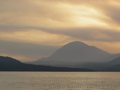 Haze from wildfires on the Kenai Peninsula hangs over Round Mountain in Cooper Landing, AK.