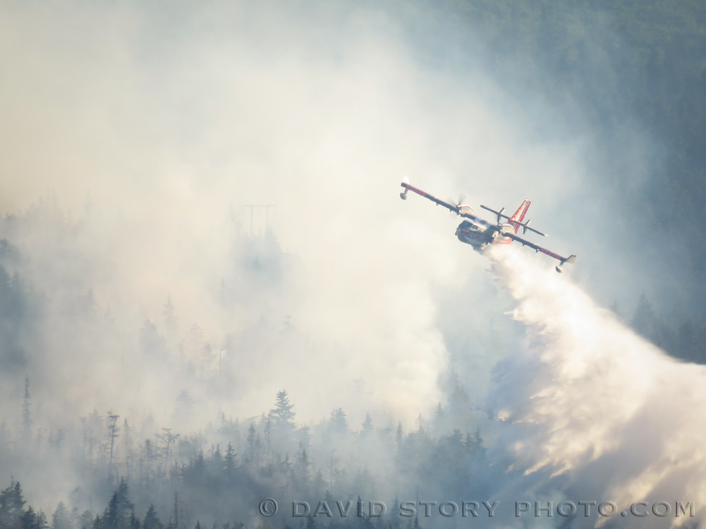 A CL-415 water scooper dumps one of many loads on the Stetson Creek Fire in Cooper Landing.