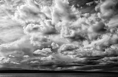 07 Apr 15	.  While joining friends on Saturday for a Easter/Resurrection Egg hunt, I was watching the clouds as they rolled off the Olympic Mountains and across the sound to where we were sitting. I probably wasn't as good a guest as I might have been, because the clouds were really holding my attention and I found myself taking a snap every so many minutes, meaning every time they appeared to have changed substantially. Looking at the clouds one might have been concerned about the potential of eminent rain, but I was more interested in both how they were moving and changing their appearance. If you look critically you will observe several different types of clouds, including those at the bottom of the shot which were dropping rain at several locations. I've added in a little grain at the bottom of the shot to emphasize that rain. While the naked eye could not see what I'm sharing, the use of a circular polarizer made it all very evident. Fortunately we were spared the rain but did get to enjoy the wonderful show in the sky.  The base image was given a small amount of contrast enhancement and then a wee bit of grain added to the lower portion of the frame only.  Nikon D300s; 18 - 200; Aperture Priority; ISO 200; 1/1600 sec @ f / 8.