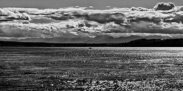 11 Feb 15.  I hadn't planned on sharing another B&W this week, but the results I was seeing on my graphics box were quite different from what I'm seeing on this box, at least with respect to the color versions, although not so with the B&W, so that's what I'm sharing. Traveling across Puget Sound one evening leaving Edmonds and crossing over to Kingston, I found it interesting how much more dramatic the clouds were with and without my glasses. I'm not talking about sharpness, that would be a given, but a difference that might best be compared to taking a photo with and without a polarizer on the lens. The detail in the clouds with and without the glasses, which are NOT polarized, was very obvious. The photos I captured were much more like what my naked eye was seeing, so I thought I'd attempt to bring back to the image what my glasses were providing for me. Around these parts, when one can see faint beams of light streaming from a cloud down into the water, they are termed sun dogs and the story is that they are drawing up water. As to the accuracy of this claim I have no idea, but generally it isn't long before we get liquid sunshine falling to the ground. In playing with this image I was able to detect some rather faint hints of sun dogs which I didn't see at the time of taking the photo(s). You look to see if you can identify them.  They do not show up in the color versions.  I took the base image and cropped off an identical amount from the top and bottom to get the composition I wanted. Next I performed a detail enhancement to bring out the texture in the clouds, but only for the clouds as they are the subject of this story. Then I performed a little dodging and burning to bring the water to a more balanced state. The sun was setting and casting some very harsh light on portions of the water's surface that I wanted to even out some, but not entirely. Then for this version I converted it to B&W and finished it off with a noise reduction layer to smooth out some graininess I introduced into the clouds as I was enhancing them. Nikon D300s; 18 - 200; Aperture Priority; ISO 200; 1/1600 sec @ f /11.