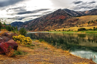 09 Jul 15.  For today's Theatrical Thursday I selected another shot from the trip I discussed yesterday. This is the same Clark Fork River but a shot from a different section of it. This image is a combination of the normal blended in with an overlay that is wildly exaggerated and then reduced in intensity. On my calibrated monitors which I employ in creating these images the over the top appearance is not nearly as significant as it is with this mail box monitor, so I have modified it on this box to look like I think it should so I don't know how it will appear on your screens. This happens ever so often, in perhaps one in a hundred images, and I've not yet determined what is causing it. It would seem like I should see the same differences in every image, but such is not the case. Hopefully the changes I just made won't deliver to you a totally blown out image. I'm thinking that as most of you don't calibrate your monitors we'll be O.K. The colors are still over the top, but that was the intent of the creative aspect. The colors in the red rocks are exaggerated, but they were there in real life, just a lot more subdued. This treatment helps you see the beauty lurking in them. The light was that of approaching evening accentuated by the developing storm.  The base image was adjusted for max tonality, given a healthy dose of detail enhancement which I removed from the hillside, then the colors red, yellow, and blue were individually adjusted, and finally I ran it through a filter to give it a dizzy look. That effect was reduced from full strength to 62%, and then applied using an overlay blend mode. The result of that is what you see. Nikon D300s; 18 - 200; Aperture Priority; ISO 200; 1/200 sec @ f / 8.