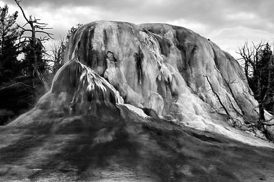 06 Oct 15.  As this is the time of year we would normally be heading to Yellowstone to enjoy the fall color, I thought I'd share a shot of my favorite thermal entity in the park. Generally I'd be sharing this in color, and as you might guess from it's name, it would be in shades of orange. But it also looks nice in monochrome, and that's what I'm sharing. When it is presented in color, I think it looses some of the character that is present in the B&W approach, although both forms provide for a nice photo. This mound is continually growing and each visit it shows us a new face so I really enjoy capturing it on each trip. The formation is located at the north entrance to the park and is one of the displays where you can park directly in front of it and either shoot it from the comfort of your vehicle or get out and walk along the boardwalk directly in front of your parking spot. The boardwalk wraps around the right hand side of the mound and is perhaps 100 feet total in length so you can easily take in the entire display even if wheel chair bound. Next time you visit the park make this one of your bullets on your must see check list. You won't regret it.  The base image was adjusted for max tonality, given a slight micro contrast adjustment, and then converted to B&W. Nikon D300s; 18 - 200; Aperture Priority;  ISO 200; 1/640 sec @ f / 9.