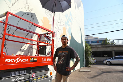Irubiel Moreno works on a mural at Mogavero Architects