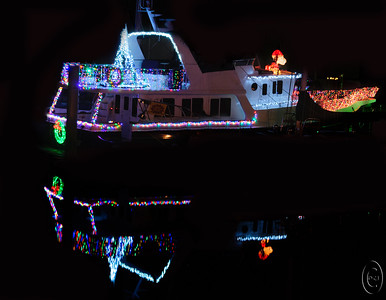 28 Dec 16.    It just wouldn't be Christmas without a shot of Christmas lights. The local community of Kingston, where we get the ferry to cross to the other side (east)  of Puget Sound, is festively decorated every Christmas starting on Black Friday and continuing until the 3rd or 4th of January. This year they added a few more decorations and I guess that's something they do each year although this year was the first time I noticed things being different. Our neighbors whose dog you know, Mini, has their boat moored in the harbor and each year they decorate it right smartly. This year was the first time I really took a look at it and under Jan's instruction took a few shots. On the bow of the boat is an inflatable Snoopy but I think they should have an inflatable Mini. I was going to make the switch but time ran out and I didn't quite get there. The marina is a bit crowded resulting in lots of stuff between the sea wall and the boats, so I had to remove a lot of stuff and rebuild several portions of Mini's boat. Mini was to be the next step. With luck next year I'll have Mini on the prow.  I straightened the base image, removed and lot of garbage and then rebuilt the boat, painting out the background clutter with black paint.  Nikon D300s; 18 - 200; Aperture Priority; ISO 640; 1sec @ f /11 on a tripod.