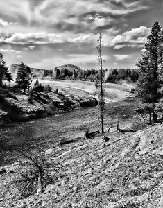 """07 Jun 16.   Our first visit into the park was just for part of an afternoon, so we elected to go to the Midway Geyser area for me to pay a visit to Grand Prismatic Spring, my favorite geothermal attraction in that part of the park. We found it quite congested at our approach which turned out to be the result of the parking lot area being """"improved."""" So we drove a bit and eventually found a spot on the side of the road where we thought we could safely park but weren't sure as there was a new set of signs this year warning all not to park on the side of the road by order of the new park czar! We parked there anyway assuming a) if they arrested us we would be in good company and b) Jan remained behind with Maggie in the vehicle not wanting to troop all the way to the spring and could always drive away!! The walk to the spring allowed for me to traverse an area that visitors aren't supposed to use - might hurt the landscape - but all the visitors were using it as it was the only approach now available to see the spring and that offered some new perspectives on the location. This one - you can see the trail to the bridge - takes you along the back side which normally you see from the opposite direction. When I saw this scene I immediately thought B&W and that is the only way I've prepared it. The clouds were quite dramatic and I could only think red filter with B&W film would be fantastic, so that was how I approached the composition. Note that the steam coming off the thermal areas is rising up to met with the clouds. It is of course something of an illusion in that the steam never touched the actual clouds, but it truly looked as though that was the case.  The base image was cropped, then converted to B&W and adjusted using a red filter.  Nikon D300s; 18 - 200; Aperture Priority; ISO 200; 1/1000 sec @ f / 8."""