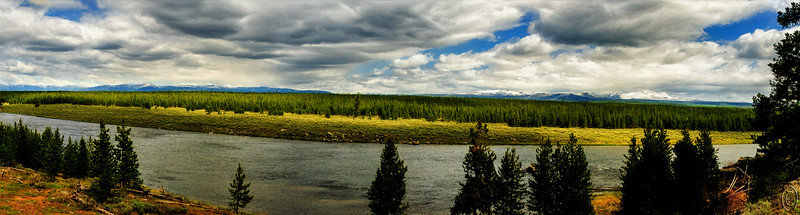 "Labor Day.    Roughly 5 miles into Yellowstone along the West Entrance Road you come to the first pullout where you also have a parking lot. Just beyond that point there are another series of pullouts sans parking lots where you can get a nice view of the Madison River with the Gallatin Range in the background. We've never seen these mountains without a lot of snow on them but as we've never visited in the summer I can't say if they are that way year round or not. Considering their height, I'm thinking they are. This shot is looking north and it's along the north shore of the river that the bison round up took place in '15 when we visited. Both the river and the road bend at this point with the road paralleling the river on it's left for about another 5 miles when the river makes a distinct dog leg to the right and the road crosses over. Often, in the early morning or late evening, you can find ""stray"" bison or elk at this location but we have yet to see more than three at a time, and generally, none. The image is a 6 shot pano so you are viewing a considerable portion of the river in this view. This is a very late morning shot and the weather that day was threatening to turn nasty but it never did save for a bit of wind. A short distance further into the park you can turn off the main road and take a side road that takes you to the rivers edge where you can drive right alongside the river. Occasionally when you do you enter a traffic jam courtesy of one or more large four legged creatures. When that occurs the best outcome occurs when you use it to get some really nice photographs paying ABSOLUTELY no attention to that thing on your wrist.  Taking all 6 images, I stitched them together and then trimmed the resultant for the best composition for my base image.The lighting that morning was quite flat, so I first gave the image some overall contrast enhancement, then used Topaz Glow 2 to get an overall look which was modified by the Darken blend mode and that constrained with a mask.  Nikon D300s; 18 - 200; Aperture Priority; ISO 200; 1/640 sec @ f /9 for all 6 images."