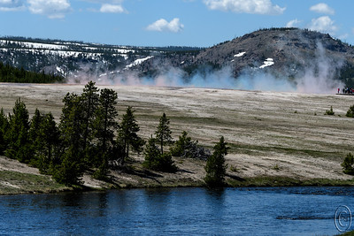 "19 Jul 17	Likely third only to Old Faithful and the Grand Canyon of Yellowstone as main attractions in Yellowstone National Park is Grand Prismatic Spring. It is my favorite of all the attractions in the geyser basin and one I always visit whenever we are there. I'll wager you have all seen a photo of it at one time or another and likely it has been an aerial view. For the last two years there has been a trail to the top of the hill behind it that was to have opened, but on each visit we are told well ""yes, but it isn't yet open"". Perhaps by 2020. The parking lot for this attraction is generally very full but in the past one could park on the shoulder of the road and walk to the access point. Now all that extra parking has been placed off limits by the new warden so getting to see it is a bit more of a challenge. Parking as we did a fair distance from the Spring we were in a location that allowed us after a short walk to view the vapor coming up off the Spring which at first might not seem like a big deal, but with the correct lighting the vapors take on the colors of the various thermophiles that carpet the Spring. As a result you get colored vapor or mist or whatever you prefer to call it. You can also see it when you are next to it but it is far more impressive when you can see a large band of it instead of just what is in front of you obscuring your view of the hot spring. Uncharacteristically of me I left in a few naked apes for perspective. Be sure to place this attraction on your Yellowstone bucket list.  This is pretty much straight from the camera aside form a little cropping for composition.  Nikon D500; 18 - 200; Aperture priority; ISO 200; 1/1250 sec @ f /10."