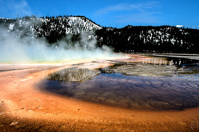 """31 Jul 17  You may recall a few days back I wrote that we have been waiting for a couple of years for the walk behind and above Grand Prismatic Spring to open lamenting that at the rate it was going it might be 2020 before it happened. No sooner had I sent that message than Jan got an email via facebook  -- ugghhhh -- that the walk had opened that very day with a picture taken from the top of the walk to prove it. So now I can go take my aerial shot and share next year.  Had serious thoughts of returning for the fall season to do it but the condo has been booked into October so that settles that. Now, thinking of the walk, perhaps I should write about some more of the things I want to see accomplished. I can think of a few. For today however we'll take another look at Grand Prismatic Spring. The spring occupies the entire bottom half of the picture and gives you some idea as to the colors found along the edge of the spring. This hot spot is a little hard to comprehend until you see it in person, but I'm hoping that once I can get a top down shot it will all make more sense. So might I suggest you hold onto the images I've shared from ground level to compare and contrast with the aerial I'll send next May.  Or for those of you who don't like to clutter up your HDs I'll just remind you to go look on the blog to make the comparisons.  And for those of you who plan on visiting and seeing for yourselves remember to allow yourself lots of time to really take it all in. A short walk along the boardwalk will not do it justice and will cheat you out of a marvelous opportunity.  I took the base image and added a tiny amount of contrast enhancement, deepened the blue of the sky to more closely match the blue color reflection in the water, and added the very faint cloud layer on the right to break up an otherwise totally boring sky. My trade off was shoot with the """"fog"""" of the spring """"helping"""" the sky but obscuring too much of the spring or going with a cleaner shot lacking clo"""