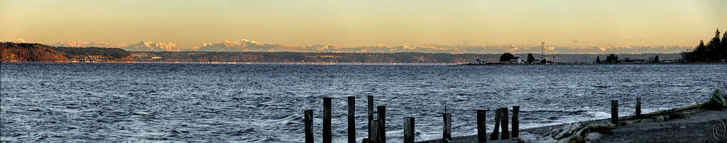 05 Jan 17	As promised , here is a shot of something I've never before seen. You are looking across a part of Puget Sound with almost, not quite, the entire range of the Cascade Mountains in view at one time. The shot is somewhat deceiving in that you are viewing roughly a 135 mile span of rock. Mt Baker is at the left had edge of the frame and Mt Rainier is out of view about an inch beyond the right hand edge and not included in the photo(s). This is a 7 frame pano. I've shared many shots from this location, but this was a first for me, to see the entire range all clearly visible, with snow no-less, at one time. For those of you who are unfamiliar with our weather this may not seem like much, but for me it was a tremendous treat so I thought I should share. The thin light line at sea level across most of the image is a mirage are frequent occurrence when looking across the sound as we are in this image. For a better idea of what is happening, watch this video. I saw this same type of activity from McMurdo Station in Antarctica.  Seven frames merged into a single composite with several adjustments made to get everything balanced.  Nikon D300s; 18 - 200; Aperture Priority;  ISO 200; 1/250 sec @ f / 5.6.