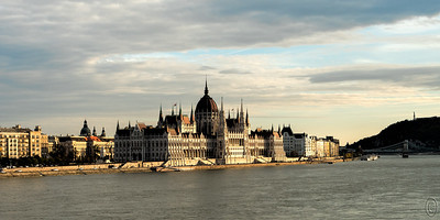 17 Apr 18	Back about 2004 I watched a video of the Red Bull Air Race that was held in Budapest flying over the Danube. Since that day I had wanted to visit Budapest simple to see the Parliament building. So when that music cruise came about it was the opportunity to see that building that convinced me I/we should go. Thus you can appreciate my great disappointment to have been joined to that major storm that made our two days there basically a wash cycle. Fortunately our additional two days brought us a little bit of better weather, with our very last day there, one which had Jan pretty much bed ridden, being actually sunny. So I did my best to see as much of the city as I could. My wanderings eventually got me crossing one of the major bridges, Margaret, and my return crossing coincided with a sinking sun bathing the Parliament building in some very golden light. I took a few snaps of that view and this is one of them. The Parliament building, a magnificent example of Neo-Gothic architecture (although displaying Renaissance and Baroque characters too), is just over 100 years old.  Other than some cropping off of the river, this is basically what we (the camera and I) saw.  Nikon D500; 18 - 200; Aperture Priority;  ISO 320; 1/640 sec @ f / 9.