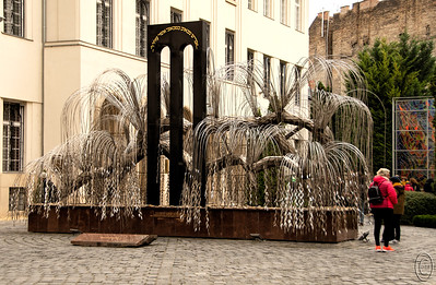 """26 Apr 18Today we take a look at a lovely piece of art commonly known, among other names, as the Tree of Life. It resides in the courtyard of the Great Synagogue in Dohany Street in downtown Budapest. I'm going to use material taken directly from the Visit Budapest web page as I think it does an """"adequate""""job of telling about the Synagogue.  We had the opportunity of visiting inside but decided against it due to time and health constraints. We likely missed out on something memorable, but since we had spent almost a quarter of a day in the Praha Synagogue we thought we had gotten a reasonable exposure to the events of WWII.  In retrospect we likely made a big mistake.  """"The Great Synagogue in Dohány Street (also known as Dohány Street Synagogue) is the largest Synagogue in Europe and the second largest in the world, capable of accommodating 3,000 people. It was built between 1854 and 1859 in Moorish Revival or Neo-Moorish style, in the wake of Romanticism. Originally, there was a residential block next to the synagogue. In fact, Theodor Herzl, founder of the Zionist movement, was born in one of the houses located there. This site is now part of the complex and home to the Jewish Museum.  During the inter-war years, anti-Semitism grew quickly in Hungary. A series of anti-Jewish policies were passed, and fascist groups like the Arrow Cross Party started to attract more followers. Hungary became an ally of Germany and the Arrow Cross Party damaged the Synagogue in 1939. During World War II, the Great Synagogue served as a stable and as a radio communication center for the Germans. Today, the compound serves as the main center for the Jewish community.""""  I copped off a couple of big distractions (tourists) on the left otherwise this is what the camera recorded. Tried my best to get a shot sans tourists but ran out of both time and patience. Nikon D500; 18 - 200; Aperture Priority; ISO 320; 1/800 sec @ f / 4.5."""