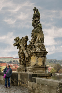 09 Jan 18	Charles Bridge would likely be included in the top 3 attractions of any list on what to see in Praha. I would agree but would quickly expand the list considerably. Today we will look at just one of the pieces of art adorning the bridge, but there are a total of 30, 15 on each side of the bridge. The vast majority of the statues were erected between 1683 and 1714, but today none remain as they have been moved to the Lapidary in the National Museum. What is now located on the bridge are exact copies. Everyone visiting sees them as the originals; I know we did and I still did until today when I was doing a search for the names of the individual statues and read about the substitutions. There is absolutely nothing to give you even the faintest idea that they are not original so don't let that dissuade you from going to see them in person. Violating my rules of no people in my pictures today by including Jan for some perspective. The real challenging part of seeing this open air art gallery is getting past the people!! We were there in late October, a time when apparently, according to our tour guide, most folks think it is the off season. It isn't.  Tourist season in Praha is roughly March through November, although based on the painting I saw on the bridge I think winter time with a nice snowfall would be one of my favorite times to visit, with fall, obviously, being the other. This is the statue of the Madonna and St Bernard (not the dog) erected in 1709, one of the last to be added. Lessor town is in the background.  Tomorrow we'll take at look at the entire gallery (bridge) in one wide photo.  Except for the sky, which I added to replace the awful gray one we experienced, this is how it looked for the brief moment when I could get people out of the frame.  Nikon D500; 18 - 200; Aperture priority; ISO 400; 1/250 sec @ f /10.