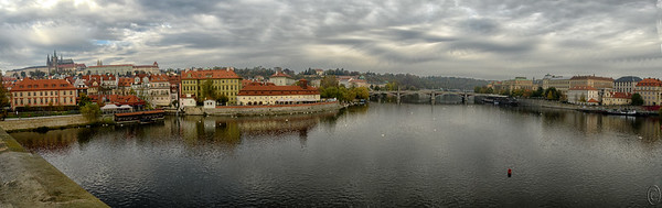 "02 Jul 18	Jumping back to Praha today for another shot from the Charles Bridge, this time looking downstream at three other bridges, of which the most distant one is showing only a tiny portion of the base. The other two are clearly visible. In the water are a few dozen swans and as you can easily tell the weather is heading to stormy. Taken in the morning, around 1000, the light was clearly that of overcast rendering the sky a perfect light box and bringing out the colors of the countryside beautifully. I'm standing near the castle end of the bridge between the statues so you don't see any of the beauty of Charles Bridge. Even zoomed in to an 18 mm focal length, this is an 8 image pano and it was necessary to get the full expanse of the river and the surrounding buildings although it does tend to distort the river some. But I like the small amount of distortion as it makes for a more impressive Moldau. With the throngs of people both visiting and locals hawking their wares, I found it refreshing to find a spot sans people, even if only a few feet wide, to just quietly stand and absorb the serenity of the scene before composing and making this ""shot."" Should you have an opportunity to visit do take some time to just relax and absorb the magnificent view.  As mentioned this is an 8 shot composite and I've cropped the composition to best display the water and sky. Nikon D500; 18 - 200; Aperture Priority; ISO 400; 1/400 sec @ f /10."