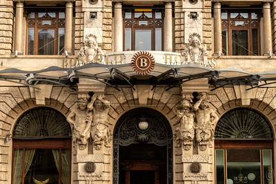 02 May 18Today we are looking at the side entrance to one of the hotels in downtown Budapest on the Pest side. If memory serves me correctly this is the Hotel New York.  The entire building from top to bottom end to end is adorned with artwork. The biggest challenge in recording it was to find a location with the least amount of abstractions in the form of guide wires, power lines, etc that compete for the eye. This shot had a minimum but still enough to be a problem. I've removed the easy stuff but gave up on that which remains. I likely could have eventually removed it but didn't want to spend a couple of hours so doing. Plus leaving in some of it gives you and idea of how it looks when you are there actually standing in front of it. I was on a street corner competing with auto, buses, and moms with strollers. It took the better part of 10 minutes to get this one shot but in the end I think it worth it.  I've cleaned up a lot of distractions but otherwise this is what the camera saw. Nikon D500; 18 -200; Aperture Priority; ISO 1000; 1/800 sec @ f / 9.
