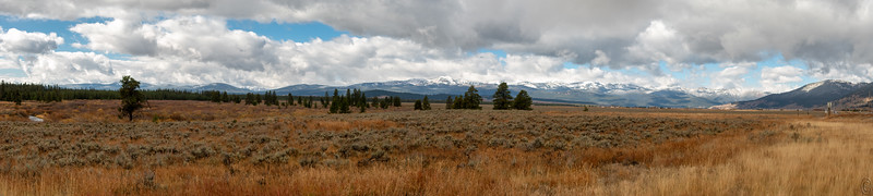 28 Nov 18Hwy 287 E & Hwy 191 S join 8 miles north of the town of West Yellowstone and continue into town where Hwy 191 ends and Hwy 287 takes a right and continues on into Idaho. At their junction you have a view of the Absaroka Range, the Gallatin Range, and the Tobacco Root Range of mountains, all part of the Rockies. On any give day the view can be anything from threatening to breath taking and everything in between. Today's submission is of the Tobacco Root Range taken from a gravel patch where the highways join and where it is safe to get off the roadway. You are looking westward and if you zoom in a fair amount at the RH edge you can read the traffic signs and see a few vehicles on Hwy 287 known at that location as Hebgen Lake Drive. This was taken on the morning after I arrived and shows a little of the freshly fallen snow from over night. Save it for a while as I'll share another taken from the same location 6 days later.  This is an 8 frame pano that I've created in Adobe Camera Raw and then given some slight noise reduction/sharpening in Topaz A I Clear. Tobacco Root Mountains  Nikon D500; 18 - 200; Aperture Priority;  ISO 200; 1/250 sec @ f /9.
