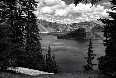 27 Aug 19	I'm seriously considering sharing another triptych for this week's images so I'm starting with a B&W which I guess is an appropriate start for B & W Tuesday. When you first enter the Crater Lake park area you of course have to stop and pay the ogre unless you have the annual or old folks pass which we, as you may surmise, have.  From there it is a short drive to the first parking lot where you find the very large visitors center where the idea is to separate you from your wallet, and the Ranger Station. Then it is perhaps another 450 foot elevation drive to the crater loop road and the park headquarters. As far as I can ascertain there are only two entrances to the loop road, north and west; we came in the west as the north was closed. There is a very limited viewing area just in front of the headquarters area before you start driving around the loop road. While we were there the loop road was open only from roughly 7 o'clock to 10 o'clock (not times), the rest still covered by snow and this was the last week in June but as you are at approximately 8K feet altitude this may not be surprising. The shot for today was taken at the first location along the loop road (real name is West Rim Drive - the only portion open) where you can clearly see the lake although only part of it. It is also the location where the cover photo for the park brochure was taken although I wasn't aware of such when I took the shot. With the obvious exception of the clouds, all the white in the shot is snow. I'm standing back about two feet from the edge - about as close as my body (nerves) would let me - when I pressed the shutter. Others were standing closer but I couldn't do it so there may be a few more trees in the shot than some would prefer; others may disagree.  This is basically straight from the camera except for my brightening the snow at the LLH edge.  A Bit Ansel-like  Nikon D500; 18 - 200; Aperture Priority; ISO 200; 1/500 sec @ f /11.