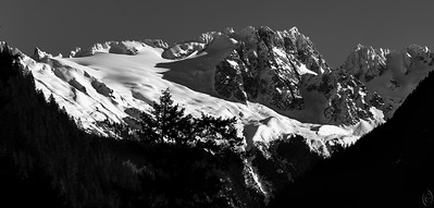 """16 Jan 19I'll press my luck and go with a second mountain image from Monday's trip up the Skagit. This time I'm going with a B&W in part because my bride, who typically doesn't like the genre, took one look and said """"that looks like an Ansel Adams print."""" Can't get a much better compliment than that so now you get to comment, at least to yourself.   I've been told the name of this peak is Lookout Mountain but I can't find any named photos to collaborate it so I'll leave it unnamed. Driving along Hwy-20 with the Skagit River on your right, at the point in Marblemount where the road and the river make a 90 degree turn to the left, there is a bridge crossing the river. The road on the other side of the bridge is Cascade River Road. This road goes about 18 miles and dead ends. At roughly the 7 mile mark is a small pull out which provides this view. This is as far as we've taken the drive as the road is generally covered in deep snow at this point and I haven't wanted to challenge Mother Nature more than necessary. Monday the road was completely dry but we had more places to visit and didn't press on. If Hwy-20 is on your horizon do take a few minutes to drive along Cascade Rive road to enjoy this magnificent view.  This is a four frame pano that I've severely cropped for best presentation. I should have taken the shot as an HDR series but failed to notice the need while I was shooting. As such the entire right hand side hillside was lost so I cropped all that away. As such you miss some of the grandeur of the location. Pano Under Harsh Lighting   Nikon D500; 18 - 200; Aperture Priority; ISO 200; 1/1250 sec @ f / 9."""