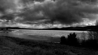 14 May 19Today being B&W Tuesday I thought I'd go with just that, a B&W image. My arrival at the condo was on the 1st of May, the earliest we had ever visited. While I expected to see things a bit different than on other trips, I wasn't fully prepared for the changes I saw. Hebgen Lake, which on a couple previous trips had been partially frozen, was almost totally frozen save for a few places along the shoreline and the very end near the park. The weather was constantly changing and when I took this shot it was switching between rain and snow. Just short showers but enough to get your attention. At places you could see remnants of snow and ice along the shoreline but otherwise it was ice all the way to the edge. By the time I departed on the 7th the vast majority of the ice had melted but about 1/4 of the lake near the Hebgen dam was still frozen. The ice had an unusual pattern on its surface, somewhat striated, and it made for an interesting sight. At places where the sun apparently spent the greater part of its time there were elliptical openings in the ice and it allowed for the blue of the water to shine through. All-in-all the weather really made this trip a hit and I hope this shot conveys same.  Other than the obvious B&W conversion, and a small amount of dodging and burning to constrain your eyes, this is what the camera saw. Just Tone  Nikon D500; 18 - 200; Aperture Priority; ISO 200; 1/1250 sec @ f / 7.1.