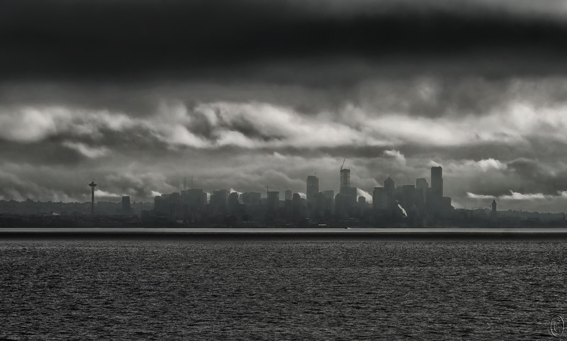 02 Oct 19Yesterday we looked at the conclusion of the first day's drive; today we look at the initiation of that drive. Stormy weather was to be the theme of the 15 day jaunt, some of it threateningly so and some of it delightfully so. We decided to take the ferry to Seattle this time to avoid the I-5 parking lot and it proved the right decision. However the ride across Puget Sound did not give us a feeling of confidence as the clouds were hanging directly overhead and were ominously dark. I was expecting a downpour any moment but we made the crossing having to deal solely with the threat. It did make for a dramatic view and so I framed the city with its two icons guarding it. On the left is of course the 605' Space Needle completed in 1962 and which is indirectly responsible for all the high rise buildings in the city. On the right is the 484' Smith Tower, the highest building west of the Mississippi River at the time of its building in 1914, and a building which was to be the tallest building in the city forever. But money talks and the ordinance forbidding anything to be taller than the Smith Tower was waived for the Space Needle . . . . .  and that opened Pandora's box. With this as the beginning of the trip, I was thinking it could only get better. In many ways it did and although we saw few animals save for multitudes of Bison, and almost no autumnal yellows in the trees, we did see some spectacular ground color and other colorful sights all of which will be forth coming. Note the presence of 13 of the new state bird, the crane.<br /> <br /> This is pretty much what the camera saw except for a small amount of contrast enhancement. Arriving  Nikon D500; 18 - 200; Aperture Priority;  ISO 100; 1/1600 sec @ f / 9.