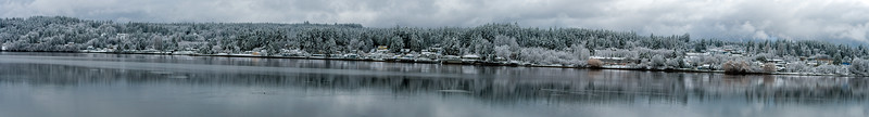 "16 Jan 20	O.K, here we go with what I had planned for the mailing yesterday. After all my moaning about missing the good weather photo-wise on Monday, it turned out that I was able to get a ""few"" reasonable captures. This is a 14 frame composite of Dog Fish Bay in Poulsbo, now renamed by the tree huggers as Liberty Bay because Dog Fish Bay just wasn't proper. There is now a nice boardwalk parallel to the road but it is out of sight as you walk down the street on the sidewalk. I probably wouldn't have gone there if not for a resident telling me to do so and I did. I wasn't immediately sure how I wanted to approach the capture but decided to shoot from the narrow end of the inlet to give a better perspective of its shape. At the far left side of the panorama on the bottom edge is the marina and park. You can, or at least on Monday you could, walk down to the finger piers and shoot. I didn't because the ramp was icy and the finger piers still covered in snow, but it might have been worth it had I been a little braver. Next good snow, if I'm still here and not in Iceland, I'll try a shoot from the finger piers working with the boats and the surrounding landscape. You'll need to enlarge this to really appreciate it.  This is a 14 frame pano stitched together that is basically what the camera recorded save for some straightening and a tiny amount of contrast enhancement. A Break in the Storm  Nikon D500; 18 - 200; Aperture Priority; ISO 200; 1/500 sec @ f / 9."