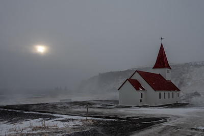 11 Jun 20Departing the sea stacks we made the short drive to the hillside above the town of Vic to visit the Reyniskyrka church, the next to last one we visited on the list of must see churches in Iceland. It was totally closed so all we could observe - when the snow let us - was the exterior. The exterior is pure white and the roof a vibrant red but it wasn't that afternoon. Being theatrical Thursday I wanted to share a creative version of the church but none of the creative ones I made adequately presented the fury of the storm, so I've elected to share the purely straight one. What looks like texture in the photo is, but not one I've added, rather, it is blowing snow. It was a real challenge to work in this weather and only three of us did any serious photography and then not for long.  Another aspect of the creative versions was that they dropped out too much of the background while this one (sorta) shows the sea stacks and a hint of the town lying at the base of the hill. A few minutes after I took this shot that feeble attempt by the sun to cast some light on the subject had concluded and it rapidly started turning dark even though it was just half past three. For the next 36 + hours we would be hunkered down in our hotel. Once safely in our hotel the biggest concern was for the van which needed both shelter from the  storm - there were no covered places to park it - and thoroughly protecting that shattered window from the battering of the wind with its 175mph gusts! Fortunately the van received nothing more than a couple small dents and was ready for us when we departed a day later. A close look at the empty area of the parking lot, especially that portion that is clearly black, will give you some idea of what the wind was accomplishing that day.  This is basically straight from the camera save for my enhancing the red of the roof a bit. To get a good idea of how the church should look you could simply use the brighten slider in your graphics program to turn 